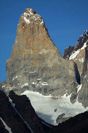 The sunlit, glacial sculpted, plutonic igneous granite spire of Torre Sur - with the snow-covered glacier below, and beyond its northern shaded buttress, to the metamorphic caprock of Cerro Fortaleza - foreground is the glacial ice streams along the lower slope of Mt. Almirante Nieto (l), and the totally cloud shaded slope of Cerro Paine (r).