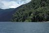 Lago Pirehueico - with the sunlit and cloud-shaded, southern beech tree forested shoreline and 4 exposed slopes - during the mid-spring season.