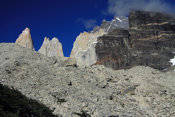 Beyond the glacial moraine, filled with till, ranging from stones to 30 ft. (9 m) boulders - to Cerro Nido Condor (r), displaying a dark metamorphic rock cap - and Cerros Norte and Central displaying solid intrusive igneous rock spires and peaks.