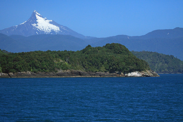 Punta Garcia to Punta Becerra, the western point of Isla Puduguapi - and above the snow-capped glacier and basalt peak, of Volcano Corcovado, rising to about 7,546 ft. (2,300 m) - Palena province - Los Lagos region.
