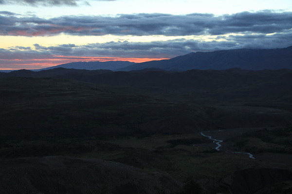 Twilight dawn glow from the eastern slope of Mt. Almirante Nieto - viewing southeastward beyond Rio Asencio, near its confluence with Lago Nordenskjold - to Sierra Toro (r) and Sierra Cazador (l), both along the distal horizon among the stratocumulus clouds.