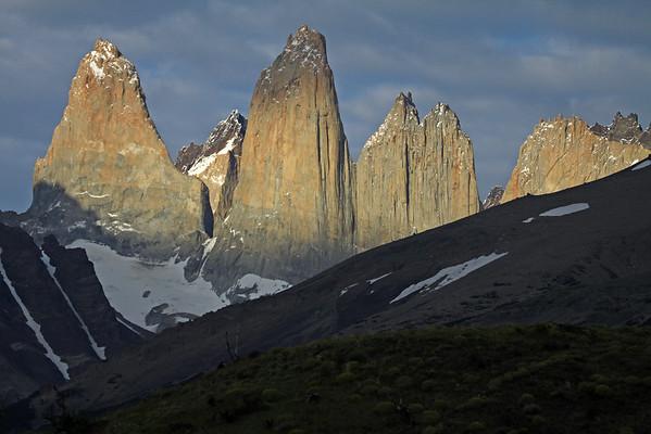Early morning sunlight upon the Towers of Paine - Torre Sur (l), and beyond its northern buttress to Cerro Fortaleza - Torre Central with its peak partially cloud-shaded, and the adjacent twin peaks of Cerro Norte - Cerro Nido Condor, displaying its jagged granite peak, and lower hornfels ridge, with a slight glimpse of the distal Cerro Escucio peak - foreground beyond the cushion plants are the shaded slopes of Cerro Paine (r) and Mt. Almirante Nieto (l), displaying its glacial ice streams.
