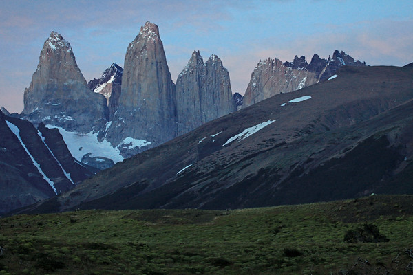 Beyond the cushion plants, to the twilight dawn upon the Torres del Paine - Torre Sur, with Cerro Fortaleza beyond - back to Torre Central, with the adjacent twin towers of Torre Norte - beyond to Cerro Escucio, and back to the jagged granite peak and lower hornfels ridge of Cerro Nido Condor - with the foreground slopes of Mt. Almirante Nieto (l), displaying its glacial ice streams, and Cerro Paine (r), with its southern beech tree forest.