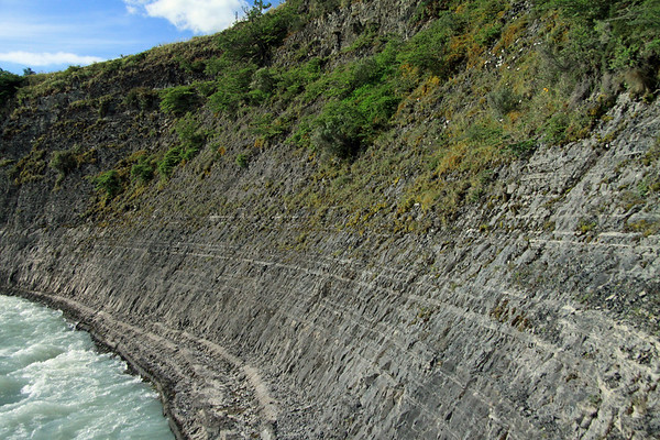 The glacial rock flour water of the Paine River - flowing along the vegetated sedimentary rock slope.