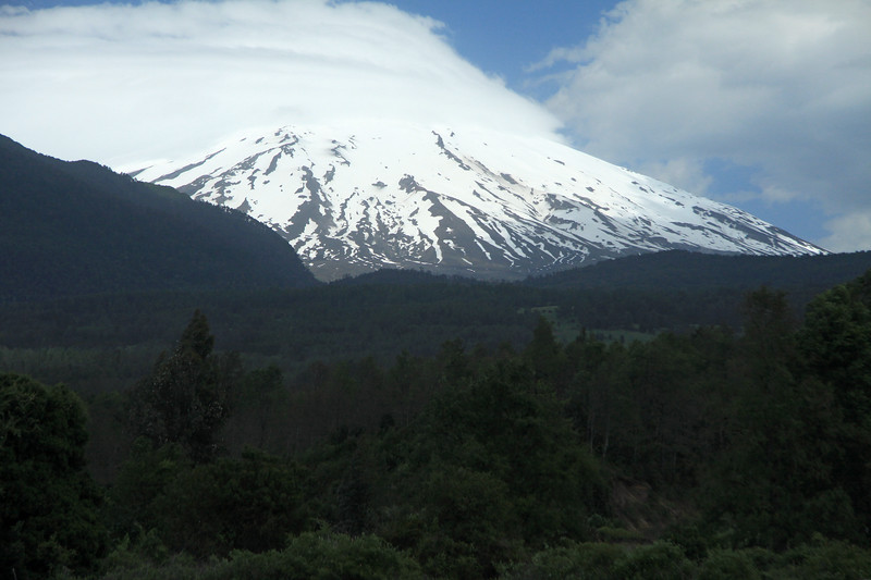 Volcan Villarrica - the southwestern snow-coated glacial ice capped slope, with its peak in the clouds - this stratovolcano is an active volcano - this image from the northeastern shore of Lago Calafquen, at the region borders of Araucania (n) and Los Rios (s) - central Chile.