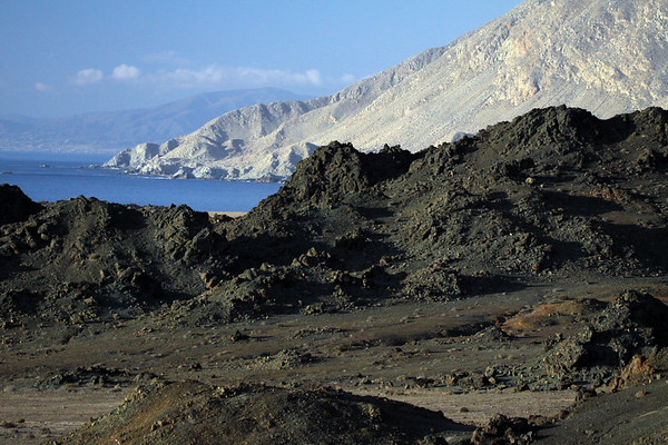 Beyond the igneous rock - to the steep coastal slopes of the Cordillera Costa, near the regional borders from here in Atacama with Antofagasta - to the distal Cerro Guanillos, among the cumulus clouds about 20 mi. (32km) northward.