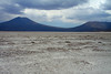 From the eastern area of the Salar Carcote, about 8 mi. (13 km) across the salt flat, then another 5 mi. (8 km) upward to the Volcan Chela (l), and nearer (r) is Cerro Pabellon.