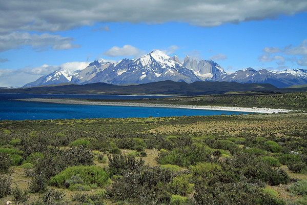 From the Patagonia Steppe ecoregion (grasses and shrubby vegetation dominating the landscape) - across Lago Sarmiento - to the Paine Massif or Cordillera del Paine, an eastern spur of the Andes Mountains - here a western view, beyond Mt. Almirante Nieto (c), Towers of Paine (r), Cuernos del Paine (l), and Cerro Paine Grande (distal, l), with its peaks in the clouds - Magellanes region, the southern most of Chile's 15 regions.