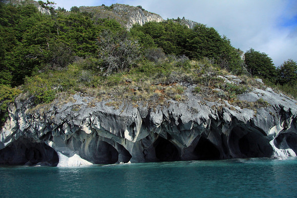 Beyond the glacial rock flour water of Lago Carrera - to the water sculpted sea caves, composed of metamorphic calcite marble - with the tussock grass, shrubs, and southern beech tree vegetation, of the Patagonia Andes above.