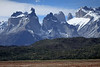 Across a field of red hued vegetation, and scrubland slopes of the Patagonia Steppe ecoregion - to the Cuernos del Paine (l) - Mt. Almirante Nieto (r) - and distal to the peaks of Torre Sur and Torre Central.