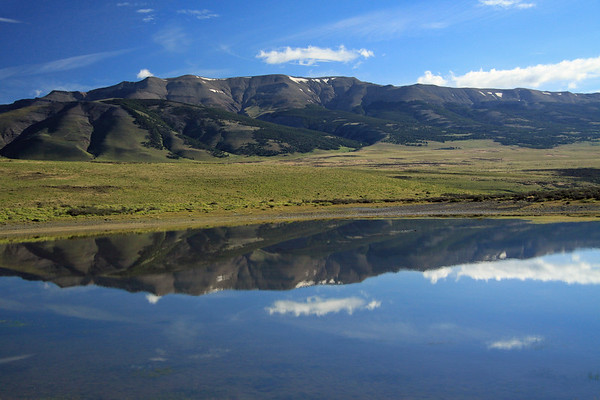 Reflection upon the placid water of an endorheic lagoon - of the Sierras Contreras, revealing the early summer season snow patches, sedimentary strata along its upper slope, and lenga beech forest along its lower slopes.
