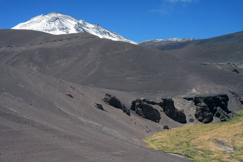 Beyond the tussock grass and  rock outcrops, along the Rio Lamas - to the snow-cloaked slope and peak of Cerro Tres Cruces Sur - Nevado Tres Cruces National Park - Copiapo priovince, Atacama Region, northeastern Chile.
