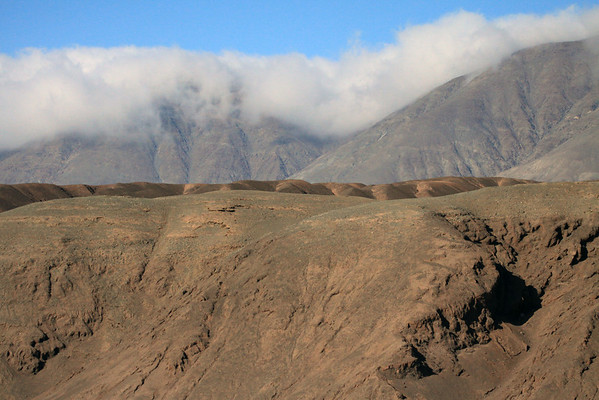 Across the iron oxide rich lower eastern slopes of Cerro Moreno, up to the cumulus clouds along its central ridge.