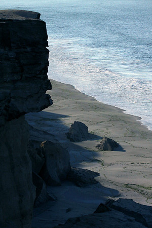 Early morning sunlight and shadows from the sea cliff ledge down to the coastline of Bahia Moreno.