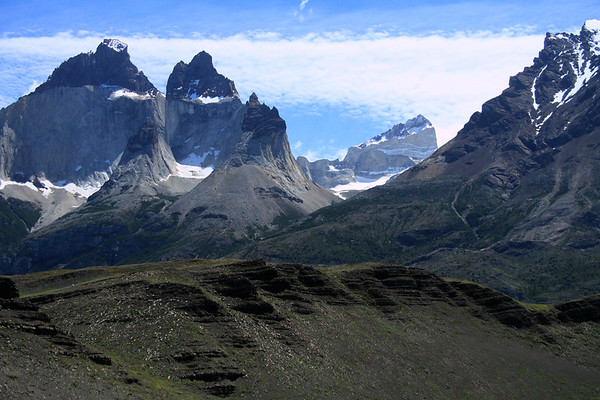 Across the shaded sedimentary rock slope - to Mt. Almirante Nieto (r) - up the couloir (steep gorge that is frequently filled with snow or ice), to East Horn, and Main Horn above (l), both comprised of a igneous granite base capped with metamorphic hornfels - to the distal La Fortaleza (fortress), rising to about 8,796 ft. (2,681 m), in the Paine Massif.