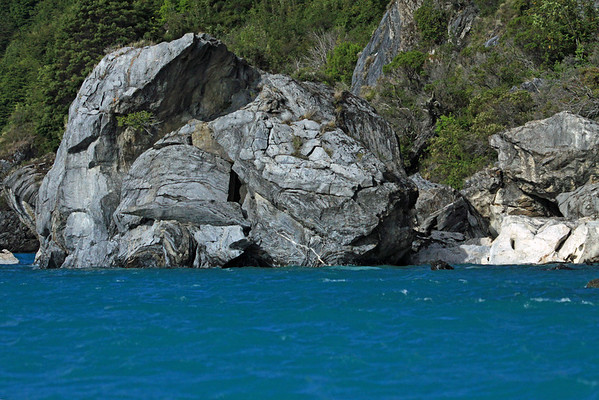 Fallen metamorphic marble scree boulders - along the western shoreline of Lago Carrera - displaying its glacial water and vegetated steep slope.