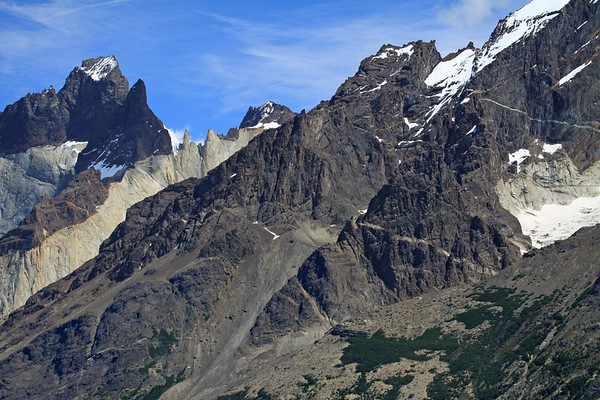 Across the southern slope of Mt. Almirante Nieto - to the cloud-shaded peak of Cuerno Este - and beyond to the snow-coated and sunlit angled peak, of Cuerno Principal - with a slight glimpse of Cuerno Norte (distal, c).