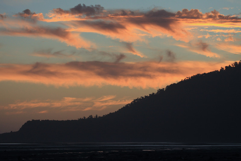 Sunset glow upon the stratus clouds, and the silhouette of the forested eastern slope and end, of Isla Puduguapi.