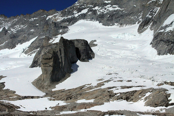 Snow-coated glacier and 2 nanutaks (an outcrop of not covered with ice or snow within or at the edge of an ice field or glacier) - here along the southeastern base of Torre Sur - with its southwestern ridge, along the naked-sky horizon.
