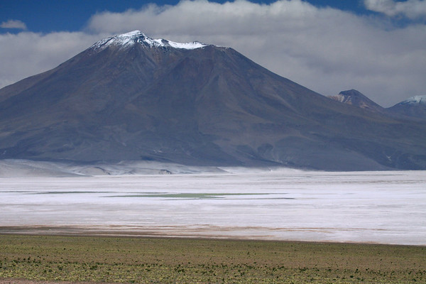 Beyond the endorheic lagoon, in the Salar Ascotan - up to Cerro Araral - beyond to the mineral-stained Cerro Ascotan Ramaditis - and the distal snow-caped Cerros Inca.