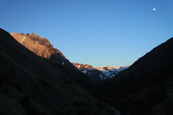 Between the morning shaded lower slopes of Mt. Almirante Nieto (l) and Cerro Paine (r), with the Rio Asencio between - to the day's first rays upon Cerro Nido Condor, and distal to Cerro Oggioni (the confluence from here along the Asencio Valley, with the Silence Valley, below the distal cumulus clouds) - and the waning gibbous moon, among the nearly naked sky.