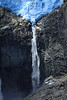 Sunlight beaming upon the terminus snout of the Ventisquero Colgante - and the plunge waterfall (vertical free-fall) descending among the igneous rock, of the Northern Patagonia Batholith - the southern Andes Mountains - Queulat National Park.