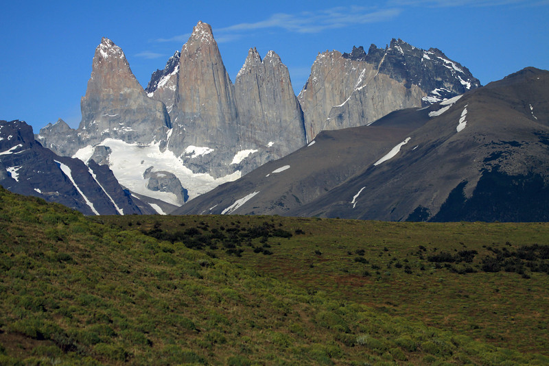 Beyond the slopes cloaked with cushion plants and shrubs - to the slope of Cerro Paine (r), revealing a forest of Lenga Beech, and lower slope of Mt. Almirante Nieto (l), and its glacial ice streams - to the Torres del Paine - Torre Sur, with the glacier below, Cerro Fortaleza (distal, r), and Cerro Negra (distal, l) - Torre Central, adjacent to the Torre Norte (showing its twin peaks) - and Cerro Nido Condor, showing its jagged granite peak, and lower hornfels ridge.