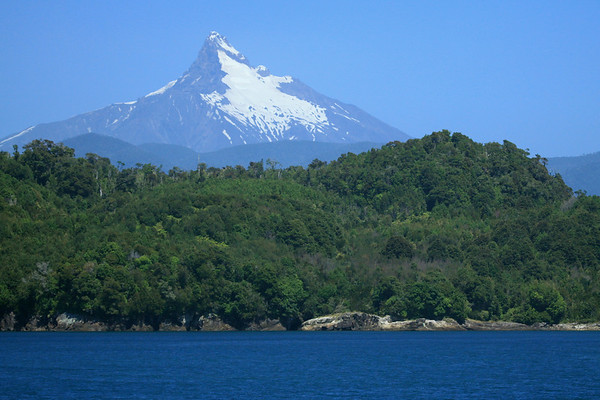 Over the igneous rock shoreline and forested slope upon Isla Puduguapi - to the glacial slope of Volcan Corcovado.