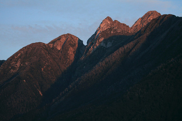 Day's past rays upon the forested slopes and igneous rock peaks - Corcovaco National Park.