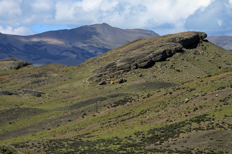 Across the sunlit sedimentary rock outcrops, scattered with cushion plants and shrubs, of the Patagonia Steppe ecoregion - to the distal sunlit and cloud shaded ridge, along Sierra Toro.