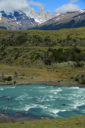 Rio Paine, displaying its glacial milk color amongst the rapids - past Cerro Paine (r) and the cloud-cloaked Mt. Almirante Nieto (l) - to the Torres del Paine - with Cerro Nido Condor, adjacent to the twin peaks of Cerro Norte - and Cerro Fortaleza, beyond Torre Central and Torre Sur.