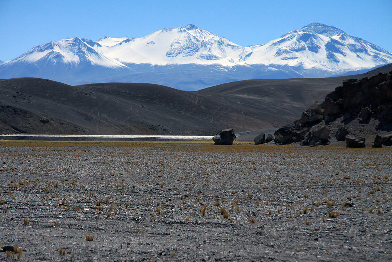 Beyond the boulder scree and southern end of Laguna Santa Rosa - beyond the lower northern slope of Cerro Pastillitos - to the snow-cloaked western slopes and peaks of Nevado Tres Cruces, 2nd highest peak in Chile, rising to about 22,139 ft. (6,748 m).