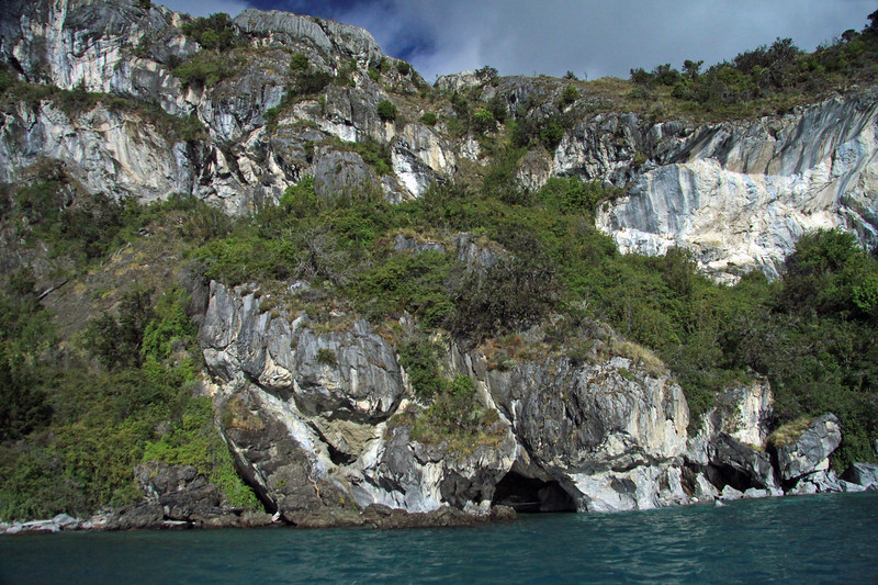 Sea caves along the marble rock - western shoreline of Lago Carrera, with its glacial milk water, and steep vegetated slopes.