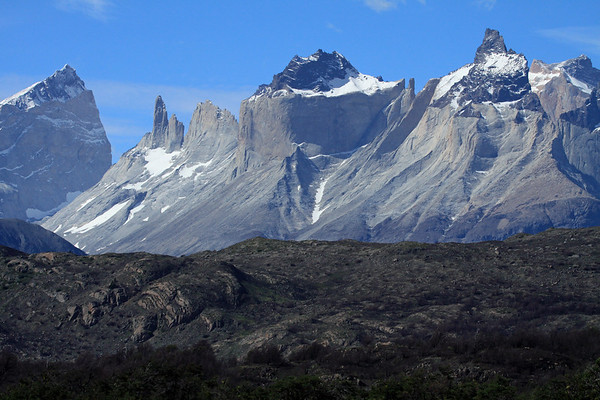 Over the rocky and vegetated ridge - to La Fortaleza (l) - next is Espada and  Hoja (the sword and blade) - then the metamorphic hornfels rock capped peaks, of the Horns of  Paine (Norte, Principal, and Este) - with the peak Mt. Almirante Nieto (distal, r).