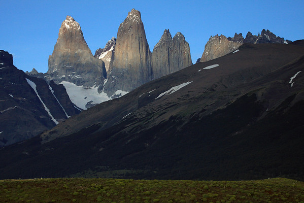 Beyond the cushion plants to the Lenga Beech forest, along the lower slope of Cerro Paine - across the Asencio Valley, to the glacial ice streams along the slope, of Mt. Almirante Nieto, and distal peak of Punta Negra upon the horizon - to the sunlit, cloud-shadowed, and majestic Torres del Paine - Torre Sur, with the glacier below, and beyond its northern granite buttress to Cerro Fortaleza, revealing its metamorphic caprock peak - Torre Central, adjacent to the twin peaks of Torre Norte - and Cerro Nido Condor, displaying its jagged granite peak, and lower metamorphic hornfels slope.