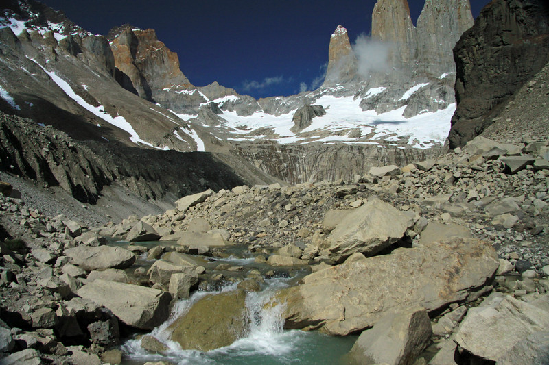 Glacial milk or rock flour water, flowing from the lagoon below Torres del Paine (distal, r) - the lower slope of Cerro Nido Condor (foreground, r), among the glacial till - the western upper slopes and ridges of Mt. Almirante Nieto (l) - and Hoya (distal, c), beyond the cumulus cloud.
