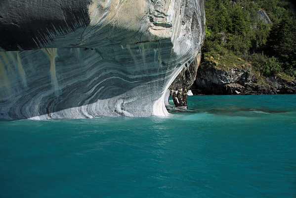 Beyond the glacial rock flour water, to overhang shadow upon the water sculpted base, of Catedral de Marmol, also displaying its arch - with the vegetated (tussock grass, shrubs, southern beech trees) and steep rocky shoreline of Lago Carrera beyond.