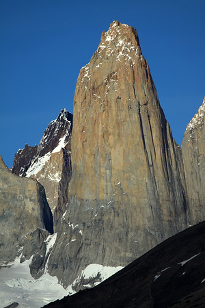 Torre Central - displaying its sunlit, glacial sculpted, plutonic igneous granite spire - attached to Torre Norte (r), by the col Bich (gap or saddle) - and adjacent to the northern buttress of Torre Sur (l), and the glacier below - and between, to the distal metamorphic caprock summit, of Cerro Fortaleza - foreground is the lower shadowed slope of  Cerro  Paine.