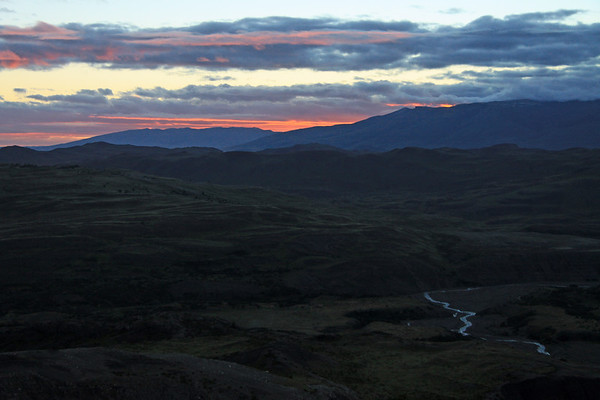 Twilght glow, near apparent sunrise - along the eastern end of Cerro Torro (r) and Cerro Cazador (l) - from the lower slope of Mt. Almirante Nieto, with the drainage basin at the northeastern end of Lago Nordenskjold (foreground).
