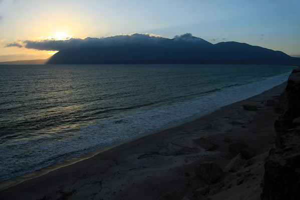 """Morro Moreno National Park (2010) - whose mountainous terrain, peaking at about 3,766 ft. (1,148 m), forms the southern end of the Mejillones Peninsula (shaped like a whale's fluke) - as seen from this sunset view from across the Bahia Moreno - Antofagasta region - the very northern most area of the Matorral ecoregion - the coastal Atacama Desert - along the Cordillera Costa - this is also the Tropic of Capricorn, at 23º 26' (Earth's boundary between the southern """"Temperate"""" zone and northern """"Tropics"""" zone."""