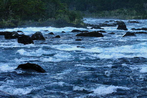 Down the rapids of the Rio Petrohue - shaded during the early morning, by the Sierra Santo Domingo.
