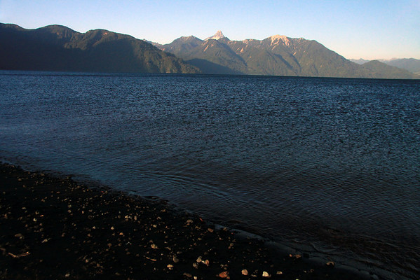 Near sunset light upon the western shoreline of Lago Todos los Santos (All Saints Lake) - to the northern forested shoreline and steep slopes, and distal conical peak of Volcan Puntiagudo.