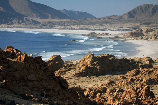 Down the sunlit and shadowed rock outcrops, scattered with scrub of the Matorral ecoregion - to the sea stack, among the waves breaking upon Playa Refugio - beyond the lower eastern slope of Cerro Castillo (l) - to the mostly shaded, Cerro Soldado.