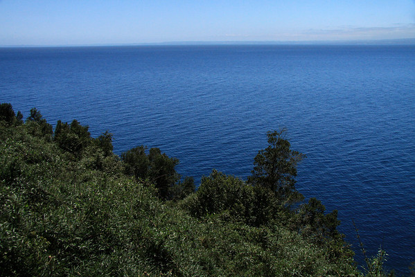 """Beyond the Valdivian vegetation, along the steep lower western slope of Volcan Osorno - down to the glacial carved, Lago Llanquihue, the 2nd largest lake in Chile, measuring about 22 mi. (35 km) long and 25 mi. (40 km) wide, with a maximum depth of about 1,040 ft. (317 m) - and Llanquilhue is the name given to the glaciation period throughout South America, back during the last glacial maximum (about 22,000 yrs. ago) when Argentina and Chile were completely covered by the Patagonia Ice Sheet from about 35°- 56° S, the """"Llanquihue Glaciation"""" - Llanquihue, means """"submersion"""" in the indigenous Mapuche language - this image viewing southwestward across the glacial lake, to the distal shoreline along the horizon."""
