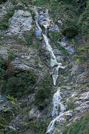 Cascade falls along the igneous rock and vegetated slope.