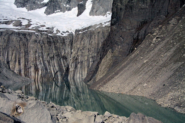 Snow-covered glacial ice below the Towers of Paine - to the early summer season's glacier melt water streaks upon the rock, reflecting upon the the calm glacial milk or rock flour water - with the the base of Mt. Almirante Nieto (r) - and till in the foreground.