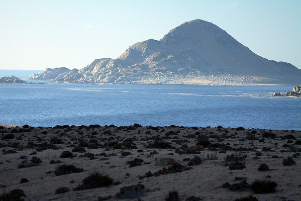 Beyond the shadowed coastal slope, scattered with xeric vegetation and a few boulders - to Isla Pan de Azucar, Sugar Bread Island - and tip of Cerro Soldado (r).