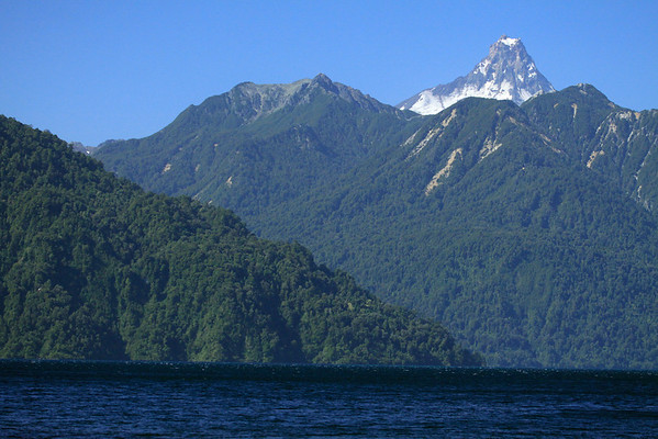 From the white-caps upon All Saints Lake (Lago Todos los Santos) - beyond the southern beech tree forested steep slopes, along the northern shoreline - to the distal extrusive igneous rock peak of Volcan Puntiagudo - Llanquihue province, Los Lagos region.