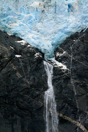 Ventisquero Colgante - displaying its mineral silt, upon the glacial ice - and its crest of a plunge falls and adjacent cascading falls - descending along the geologic stratum.
