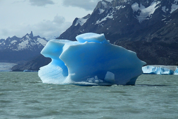Beyond a bergy bitt to a couple of blocky icebergs, afloat Lago Grey - and the slopes of Cerro Paine Grande (r) - to the terminus snout of Grey Glacier - and the distal Cerro Punzon and Cerro Piramide.
